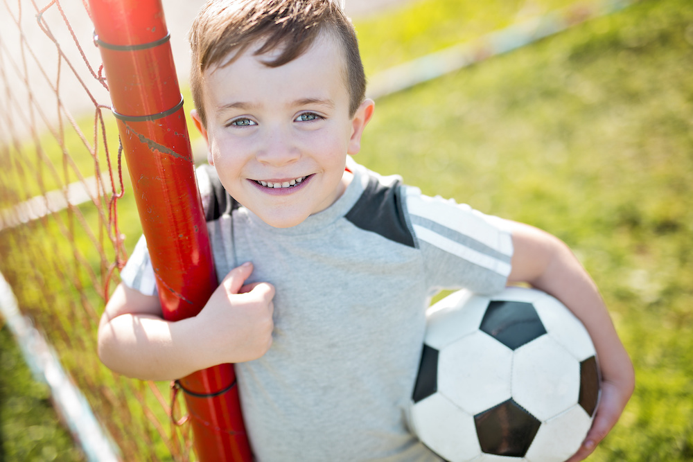 young boy holding soccer ball - needs school sports physicals