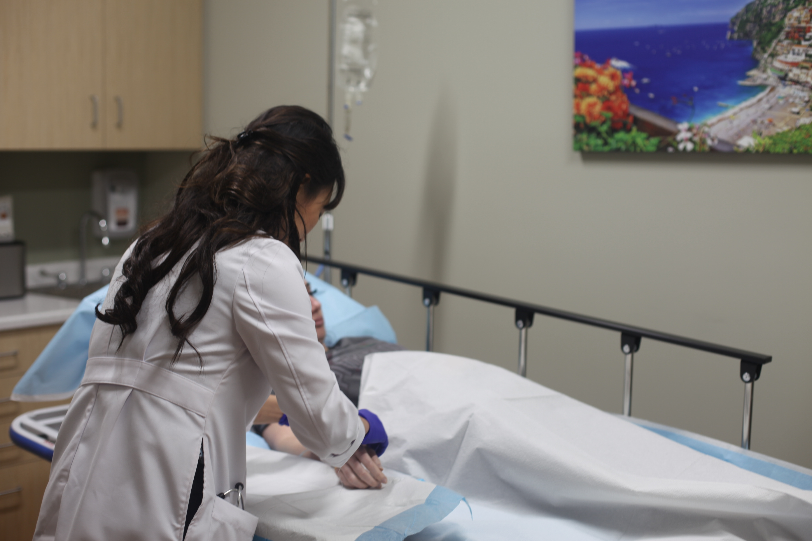 Dr. Yi Zhang providing treatment to patient for common illnesses and injuries