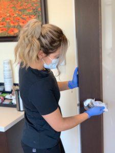 image of haven elite staff member disinfecting door handle